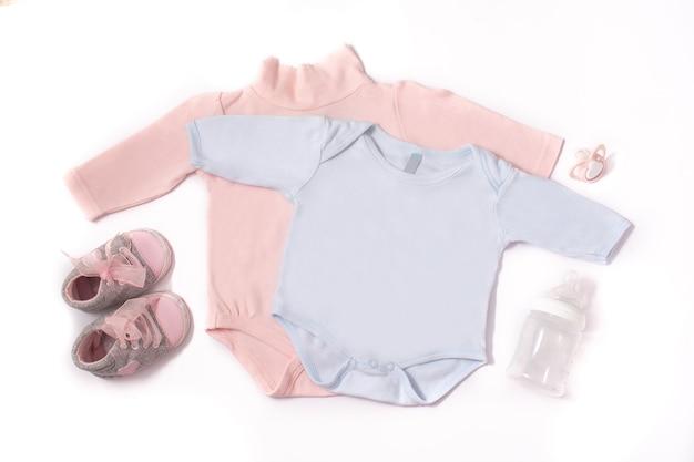 Baby pagliaccetti, scarpe, biberon e ciuccio isolati su sfondo bianco Foto Premium
