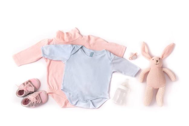 Pagliaccetti, scarpe, biberon, ciuccio e coniglietto giocattolo isolati su priorità bassa bianca Foto Premium