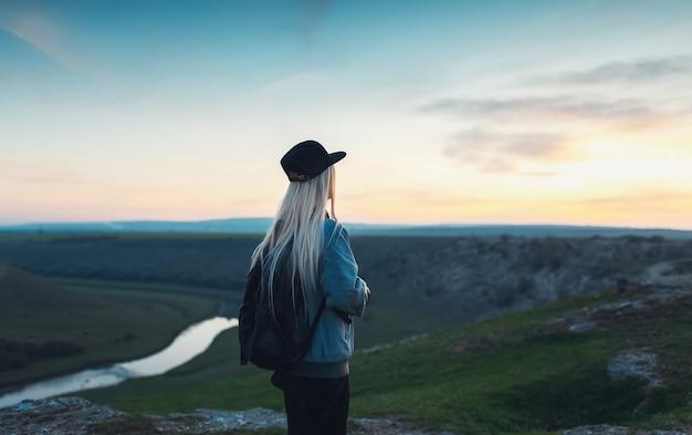 Vista posteriore della ragazza bionda con zaino nero e cappuccio. giovane viaggiatore guardando il tramonto dalle colline. Foto Premium