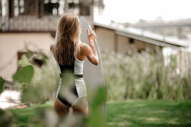 Punto di vista posteriore del costume da bagno sexy biondo della donna in bianco e nero che sta con il wakeboard Foto Premium