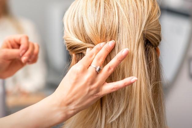 Vista posteriore della mano femminile del parrucchiere modella un'acconciatura di una giovane donna bionda in un parrucchiere Foto Premium