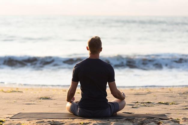 Uomo di vista posteriore che fa yoga sulla sabbia Foto Premium