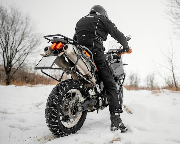 Vista posteriore uomo in sella a una moto il giorno d'inverno Foto Premium