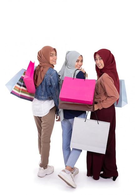 Vista posteriore di tre donne hijab che trasportano sacco di carta dopo lo shopping insieme Foto Premium