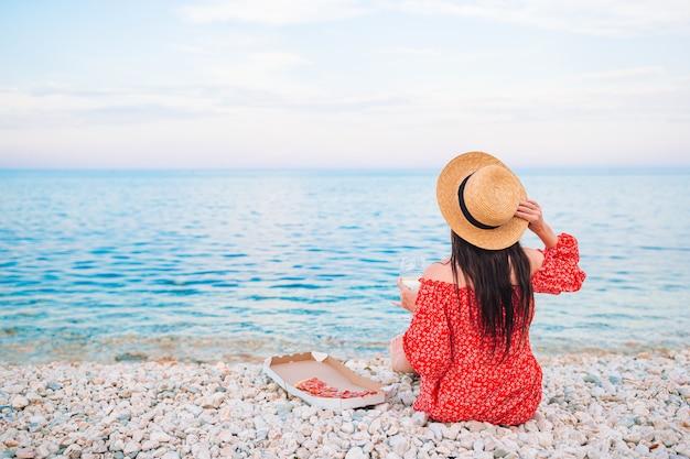 Punto di vista posteriore della donna sulla spiaggia sul picnic che esamina il mare Foto Premium