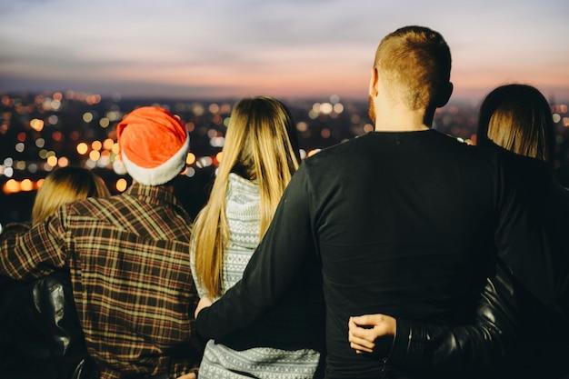 Vista posteriore di giovani che si abbracciano e ammirano la vista della città sfocata mentre si celebra il natale di notte Foto Premium