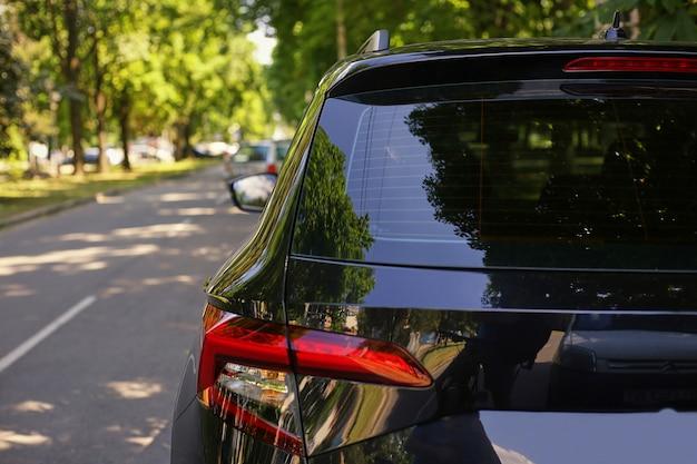La finestra posteriore dell'automobile nera ha parcheggiato sulla via nel giorno soleggiato dell'estate, retrovisione. mock-up per adesivo o decalcomanie Foto Premium