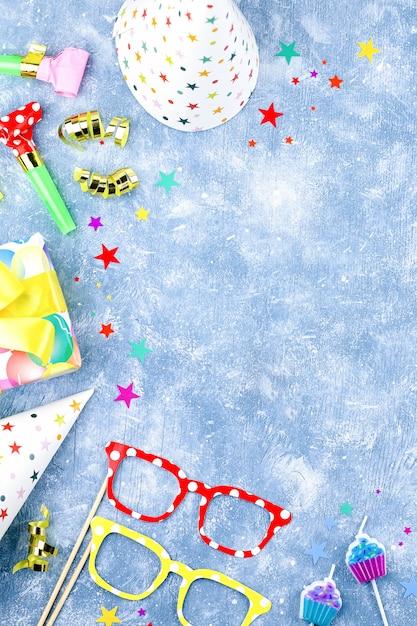 Sfondo con regali avvolti, coriandoli, cappelli da festa, decorazioni, copia spazio Foto Premium