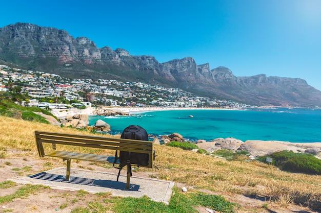 Zaino del viaggiatore solitario su una panchina in vista della splendida spiaggia di camps bay a cape town, sud africa Foto Premium