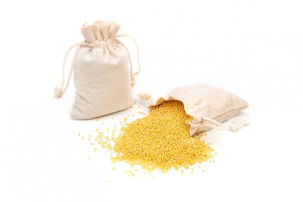 Borsa di miglio di cereali giallo su uno spazio bianco Foto Premium