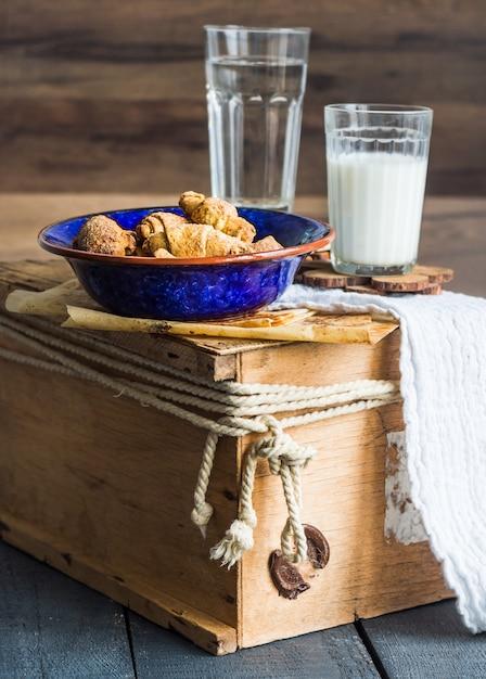Biscotti bagel da una pasta frolla con ripieno, latte, nel piatto blu pasticceria dolce su un legno Foto Premium
