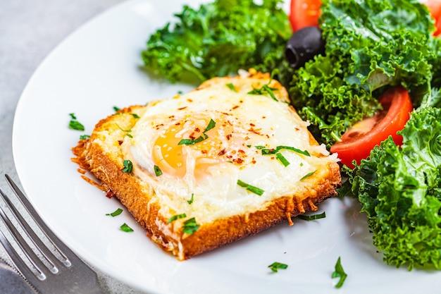 Uova al forno e pane tostato con insalata su un piatto bianco, primo piano. Foto Premium