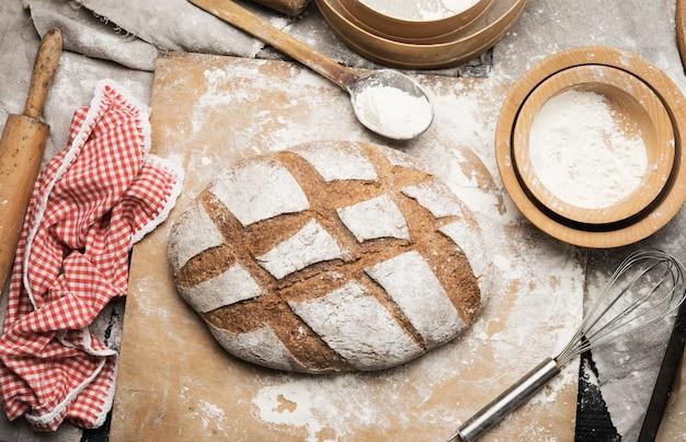 Pagnotta di pane al forno sul tavolo e ingredienti, utensili da cucina si trovano nelle vicinanze, vista dall'alto Foto Premium