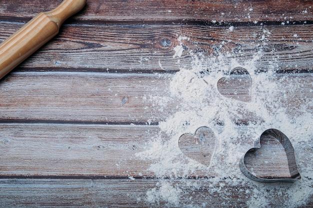 Sfondo di cottura con farina e forma di cuore sul tavolo da cucina scuro con spazio per il testo. Foto Premium