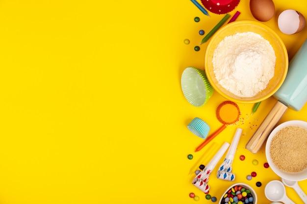 Ingredienti del bigné di compleanno di cottura su fondo giallo, disposizione piana Foto Premium