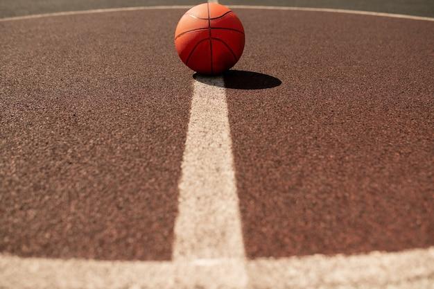 Palla per giocare a basket che si trova al centro della linea bianca verticale sul moderno stadio o campo Foto Premium