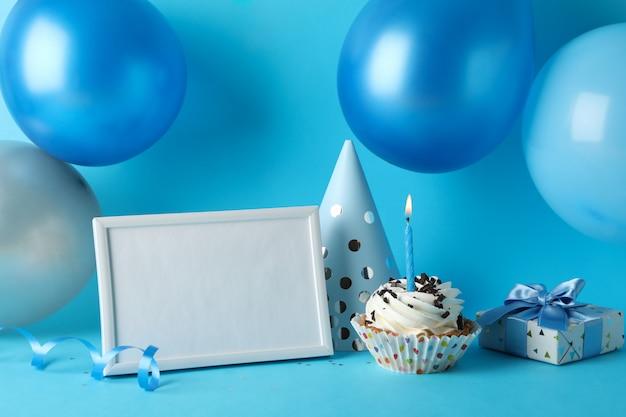 Palloncini, cappello compleanno, cupcake, cornice e confezione regalo su sfondo blu, spazio per il testo Foto Premium