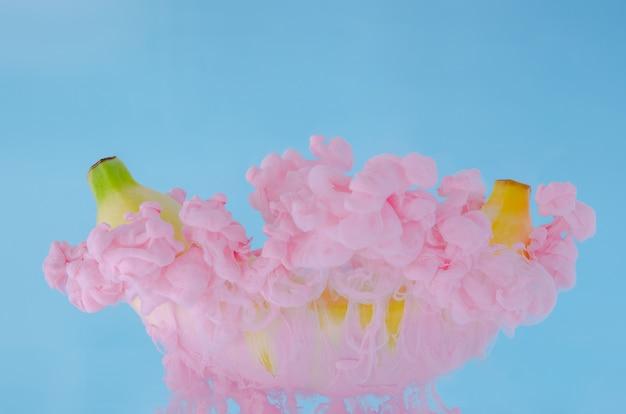 Un frutto di banana con parziale attenzione alla dissoluzione del colore rosa del poster in acqua su sfondo blu. Foto Premium