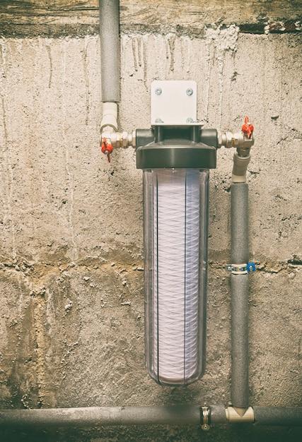 Una fascia nuova per il filtro dell'acqua con tubi di plastica nel seminterrato Foto Premium