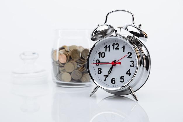 Banca con monete e primo piano sveglia. il tempo è il concetto di denaro Foto Premium
