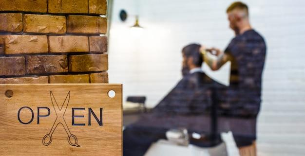 Salone da barbiere. apri barder shop. parrucchiere o barbiere. uomo in visita dal parrucchiere nel negozio di barbiere. Foto Premium