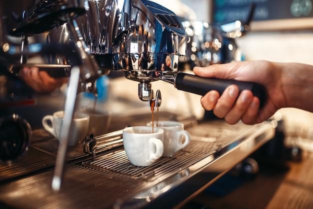 La mano del barista versa la bevanda dalla macchina del caffè Foto Premium