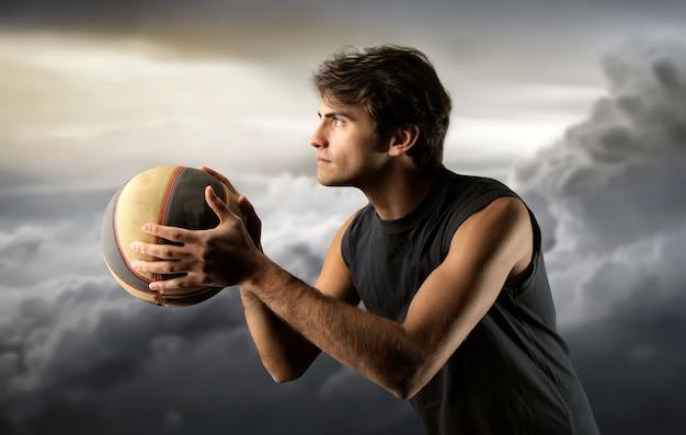 Giocatore di pallacanestro e un cielo nuvoloso Foto Premium