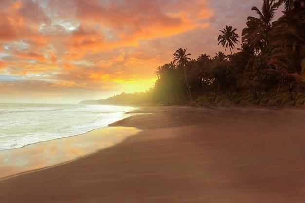 Vista della spiaggia nel pomeriggio con un tramonto in fiamme Foto Premium