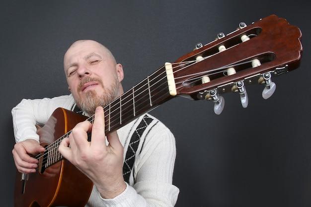 L'uomo calvo barbuto suona la chitarra classica Foto Premium
