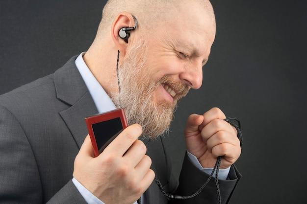 L'uomo d'affari barbuto ama ascoltare la sua musica preferita a casa con un lettore audio in piccole cuffie. audiofilo e amante della musica. musica e suono hi-fi. Foto Premium
