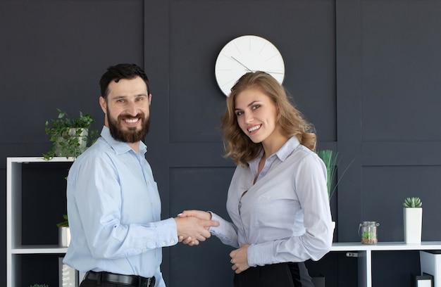 Imprenditore barbuto e imprenditrice agitando le mani in ufficio Foto Premium