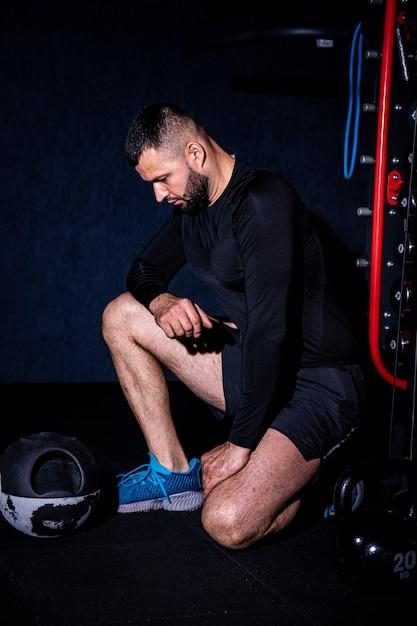 Uomo atletico muscoloso bello barbuto con un asciugamano nello spogliatoio dopo aver lavorato. Foto Premium
