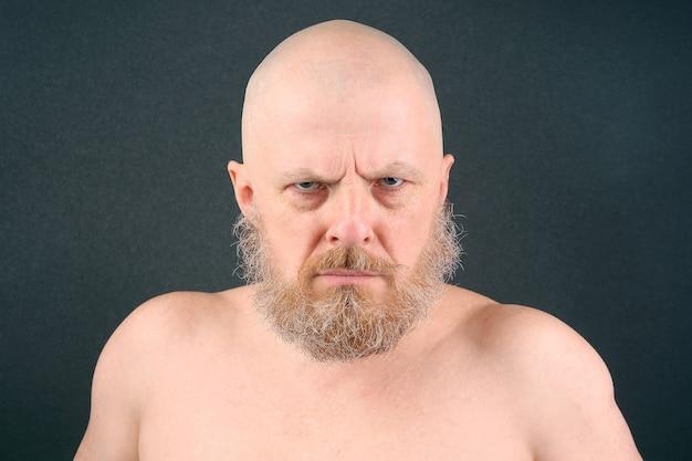 L'uomo barbuto dall'aspetto aggressivo guarda negativamente avanti Foto Premium
