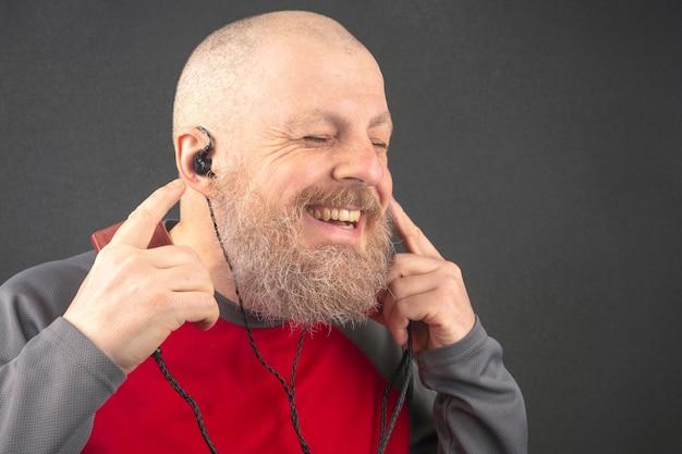 L'uomo barbuto gode di ascoltare la sua musica preferita attraverso un lettore audio in piccole cuffie. Foto Premium
