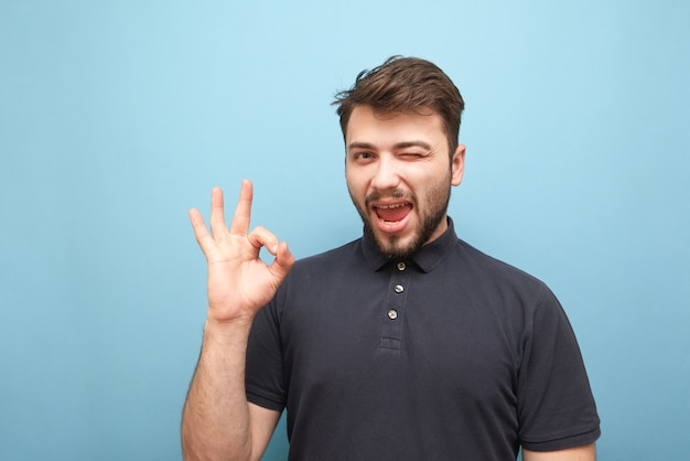 L'uomo barbuto mostra ciò che gli piace isolato su giallo Foto Premium