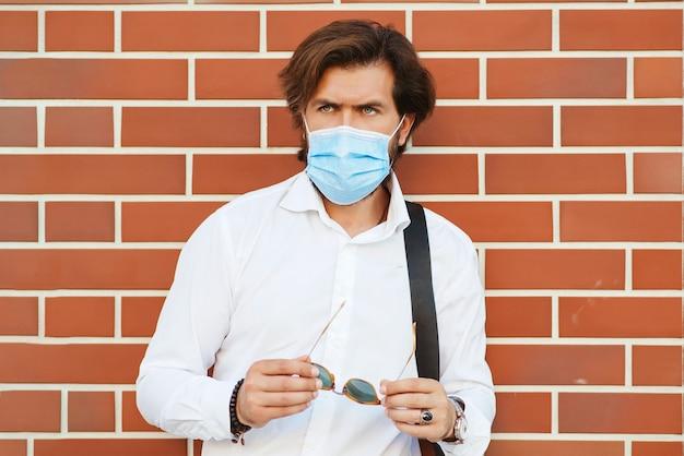 Uomo barbuto che indossa la maschera per il viso all'aperto. uomo barbuto alla moda in camicia bianca con borsa. Foto Premium