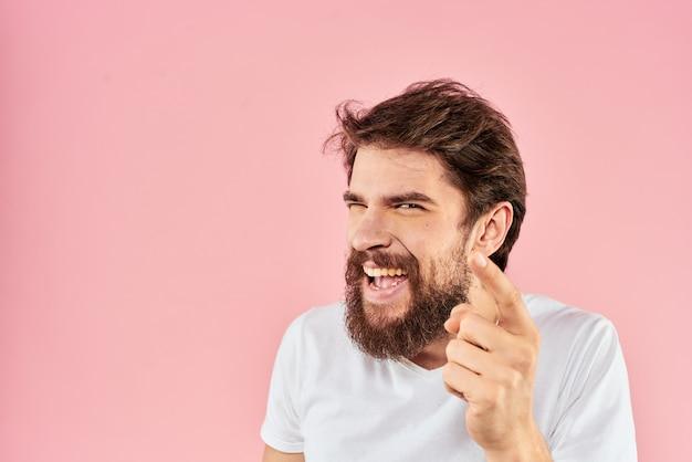 Uomo barbuto in maglietta bianca gesticolando con le mani espressione facciale close up rosa. Foto Premium