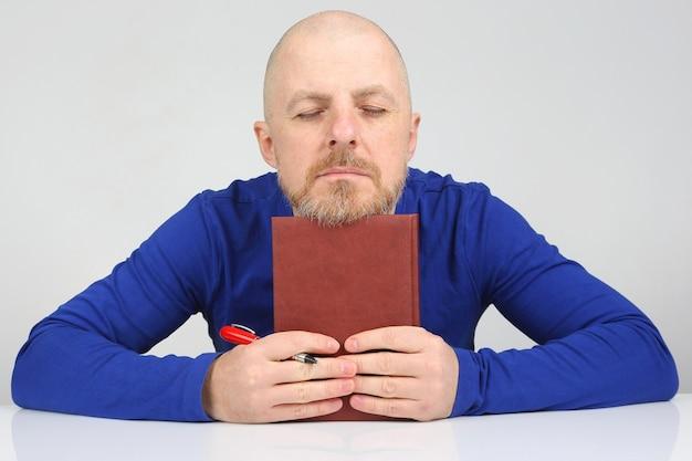 Pensa l'uomo barbuto con un taccuino e una penna in mano Foto Premium