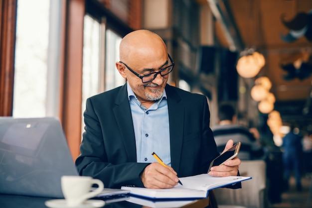 Uomo d'affari senior barbuto che esamina lo smart phone e che scrive le attività nell'ordine del giorno mentre sedendosi nel self-service. Foto Premium