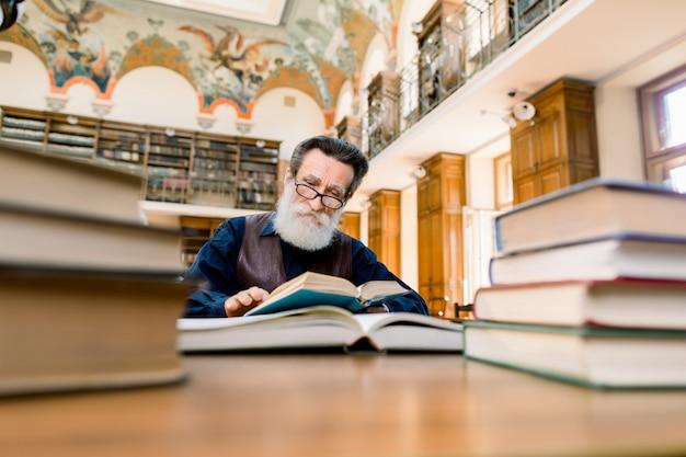 Barbuto uomo anziano, scrittore, scienziato, insegnante, amante dei libri, seduto nella vecchia biblioteca della città vintage al tavolo con molti libri e leggendo un libro Foto Premium