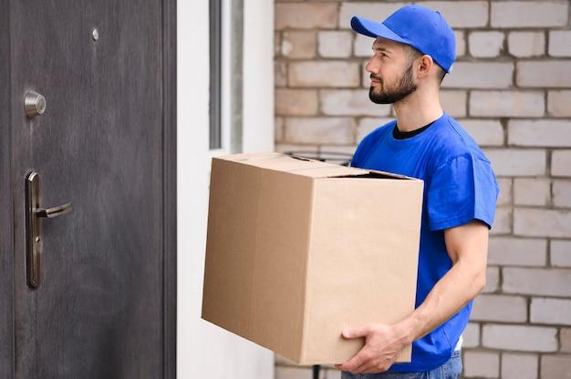 Giovane barbuto pronto a consegnare scatola Foto Premium