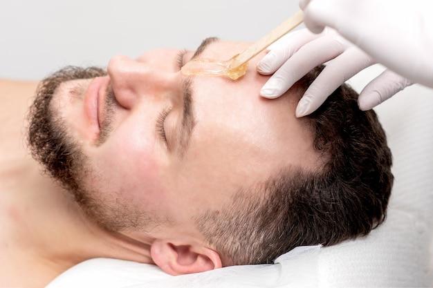 L'estetista applica la cera tra le sopracciglia maschili prima della procedura di ceretta nel salone di bellezza. Foto Premium