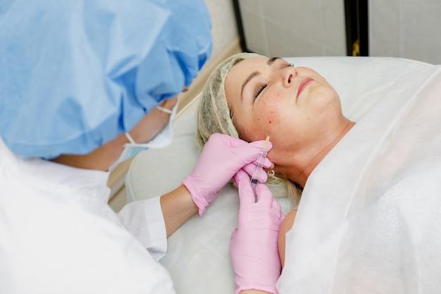 Estetista che fa iniezione facciale per donna. procedura cosmetologica di rivitalizzazione antietà Foto Premium