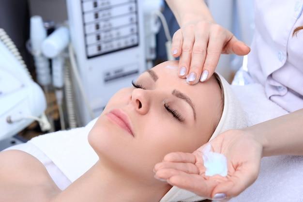 L'estetista fa la pulizia e l'esfoliazione del viso per una bella ragazza. salone di bellezza. Foto Premium