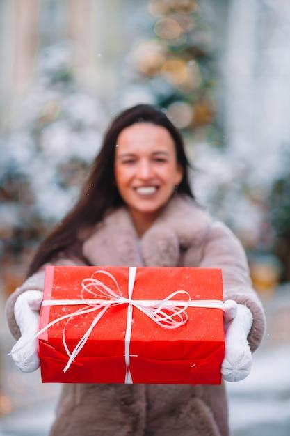 Beautidul donna vicino all'albero di natale nella neve all'aperto Foto Premium