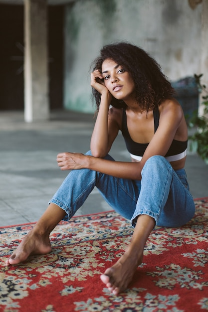 Bella ragazza afroamericana con capelli ricci scuri in top sportivo nero e jeans pensieroso mentre era seduto sul tappeto vintage a casa Foto Premium