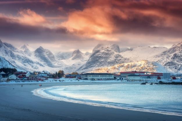 Bella spiaggia sabbiosa artica con il mare blu in inverno al tramonto Foto Premium