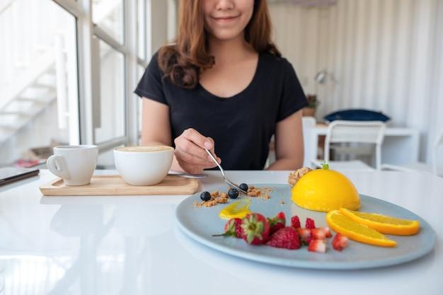 Una bella donna asiatica che mangia torta arancione con frutta mista con un cucchiaio nella caffetteria Foto Premium