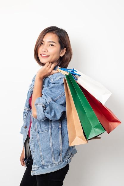 Sacchetti della spesa sorridenti della tenuta della bella giovane donna asiatica Foto Premium