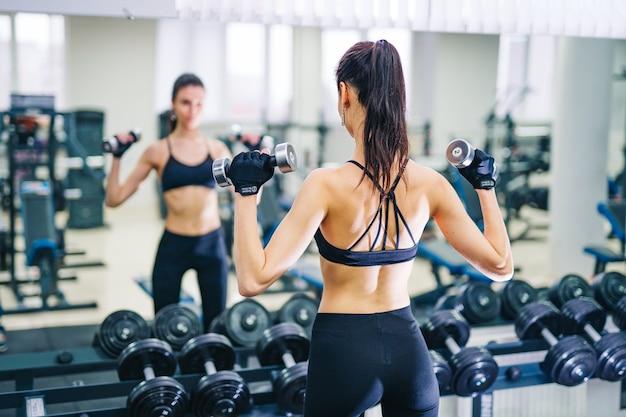 Bella giovane donna atletica che fa esercizio in palestra. giovane donna con corpo muscoloso. concetto di fitness. Foto Premium